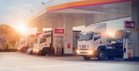 Photographie de plusieurs poids lourds alignés dans une station-essence.